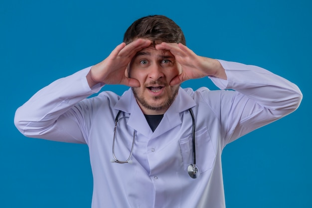 Young man doctor wearing white coat and stethoscope surprised looking far away with hand over head over isolated blue background