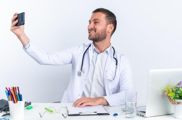 Giovane medico in camice bianco e con lo stetoscopio facendo selfie utilizzando smartphone felice e positivo sorridente allegramente seduto al tavolo con il computer portatile su bianco