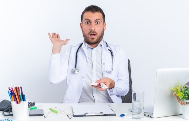 Young man doctor in white coat and with stethoscope holding different pills amazed and surprised sitting at the table with laptop on white