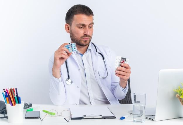 Giovane medico in camice bianco e con lo stetoscopio che tiene diverse pillole guardandole con faccia seria seduta al tavolo con il computer portatile su sfondo bianco