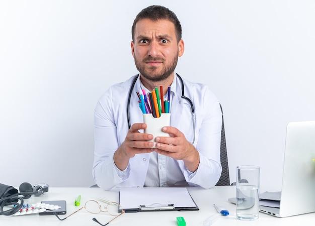 Medico del giovane in camice bianco e con lo stetoscopio che tiene le matite che sembra confuso seduto al tavolo con il computer portatile su sfondo bianco