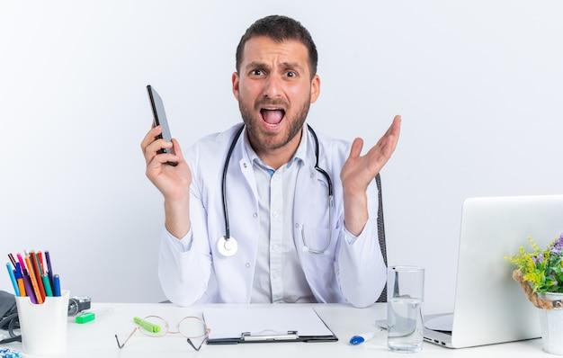 Giovane medico in camice bianco e con lo stetoscopio che tiene lo smartphone confuso seduto al tavolo con il computer portatile su un muro bianco