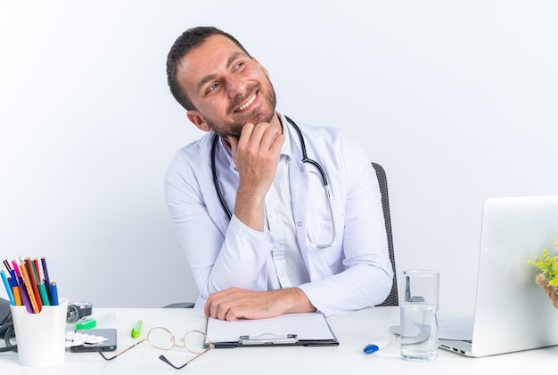 Young man doctor in white coat and with stethoscope looking up happy and cheerful smiling broadly sitting at the table with laptop on white