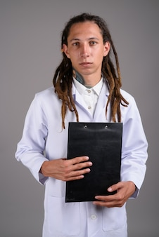 Young man doctor with dreadlocks against gray background