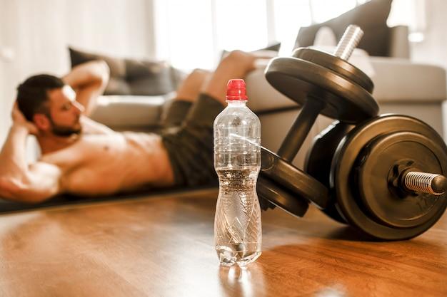 ソファで自宅で腹筋運動をしている若い男。彼のアパートでのエクササイズアクティビティでハードウォーキングのtシャツのない男のスポーツマンのビューをカットします。床に横になっている写真のダンベル。