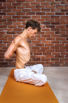 Young man doing breathing practices of belly, abdominal vacuum exercise.