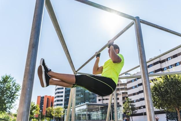 Young man doing calisthenics on pull-ups bar outdoors.
