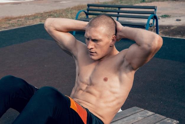 Молодой человек делает упражнения на скручивания на тренировке мышц брюшной полости и груди на стадионе