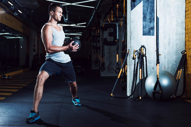 Young man doing exercise with medicine ball