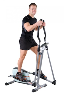 Young man doing exercises on elliptical trainer