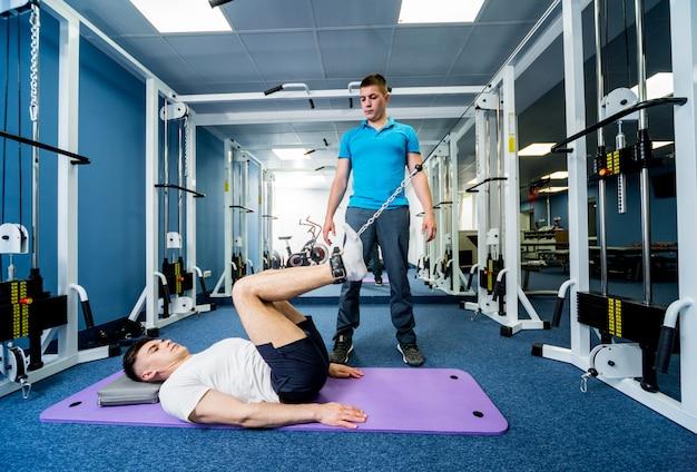 물리 치료사의 감독하에 매트에 운동을하는 젊은 남자.