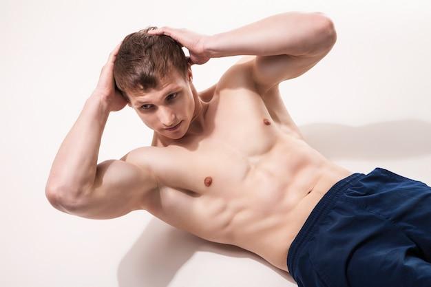 スタジオの床でエクササイズをしている若い男