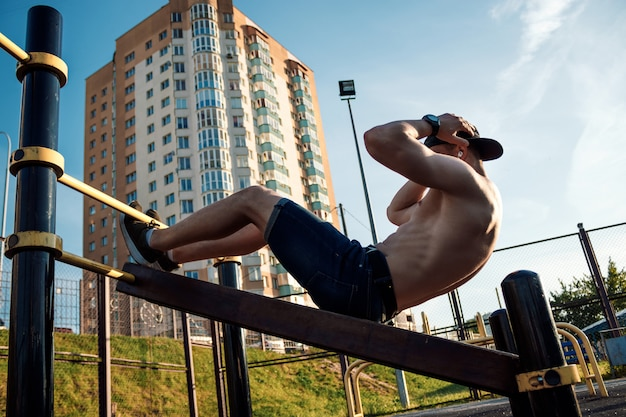 Young man doing exercisethe press on the sports field, athlete, outdoor training in the city