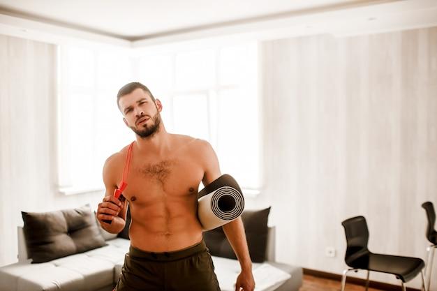 若い男がソファで自宅で運動をしています。ヨガマットと縄跳びをしている