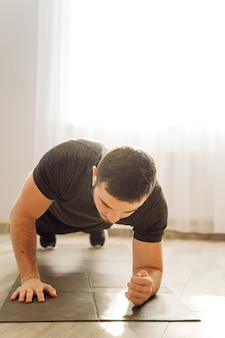 Young man doing fitness exercise at home