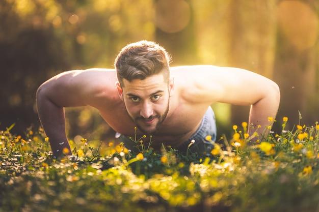 Молодой человек делает сгибания в природе