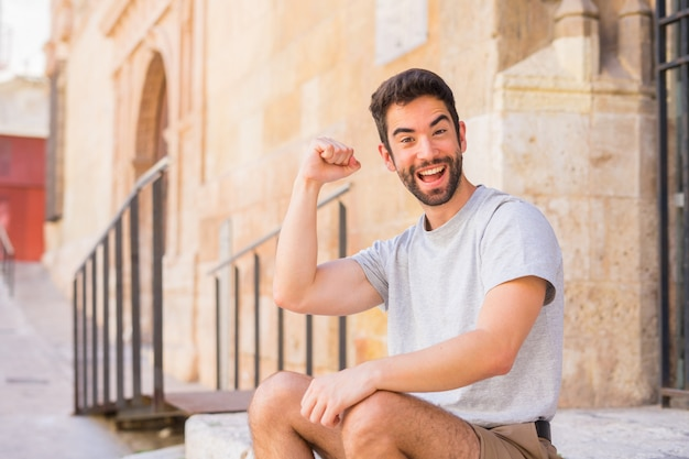 Young man doing gesture of success in the street