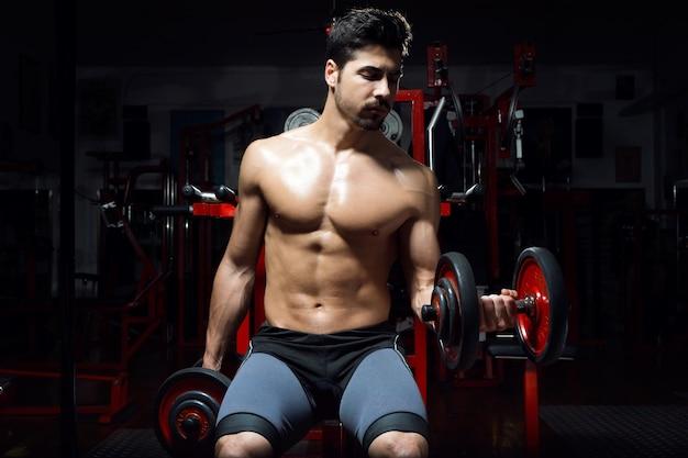 ジムで重い運動をしている若い男。