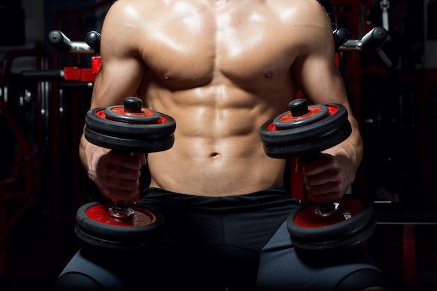 Молодой человек делает тяжелые упражнения в тренажерном зале.