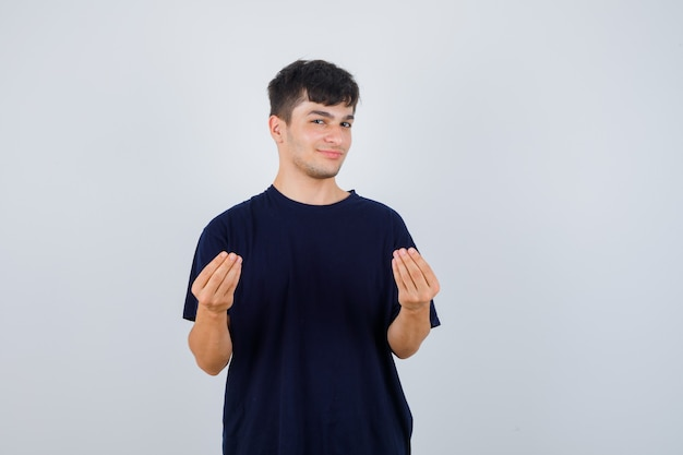 Giovane che fa gesto italiano in maglietta nera e sembra fiducioso, vista frontale.