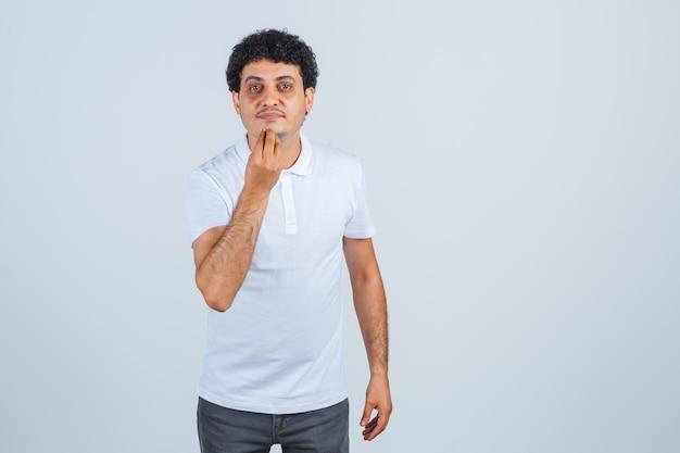 흰색 티셔츠, 바지, 자신감 있는 표정으로 이탈리아 제스처를 하는 젊은 남자. 전면보기.