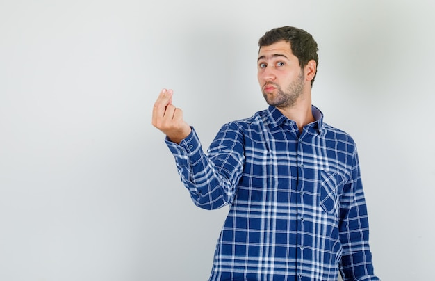 Young man doing italian gesture with fingers in checked shirt