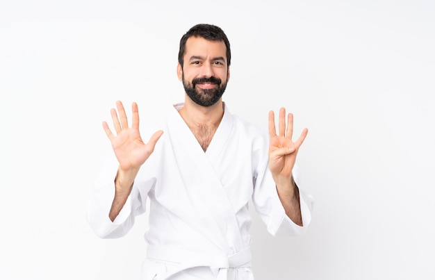 Young man doing karate over isolated  counting nine with fingers