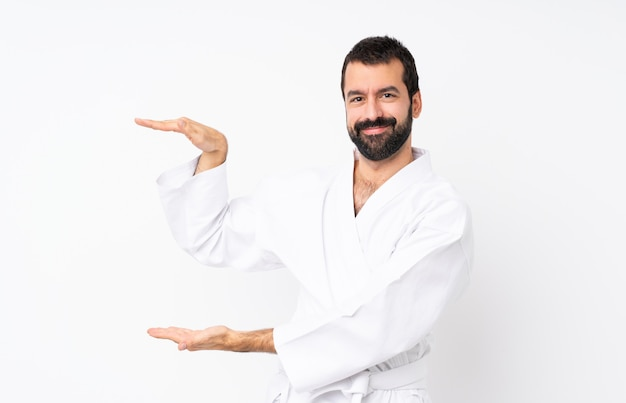 Young man doing karate over isolated  holding copyspace to insert an ad