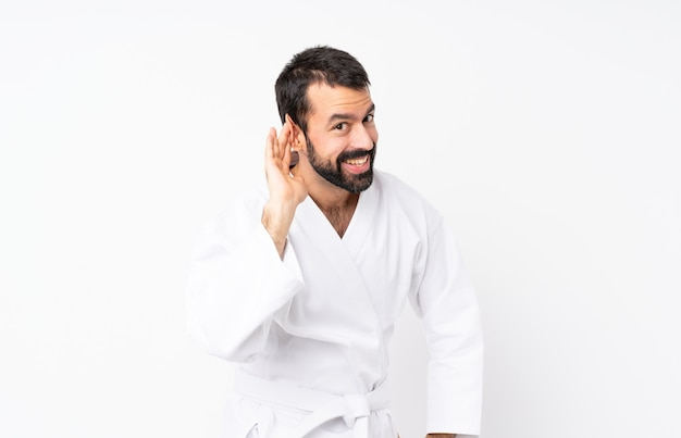 Young man doing karate over isolated  listening to something by putting hand on the ear