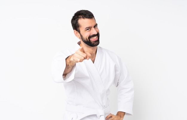 Young man doing karate over isolated  points finger at you with a confident expression