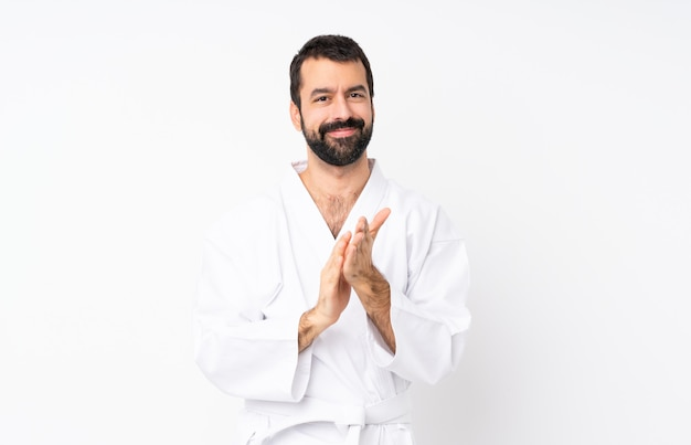 Young man doing karate over isolated white applauding after presentation in a conference