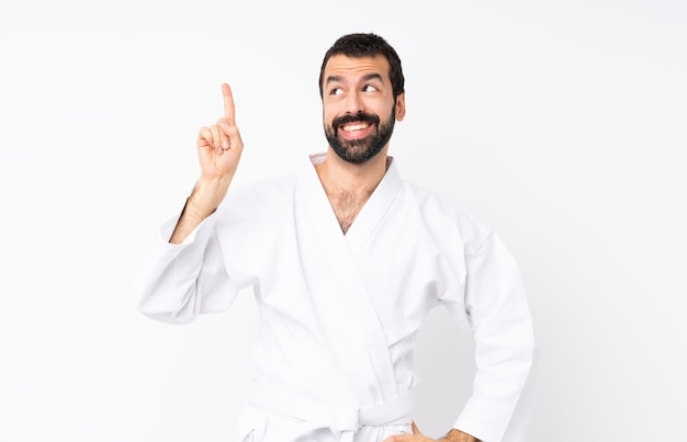 Young man doing karate over isolated white intending to realizes the solution while lifting a finger up