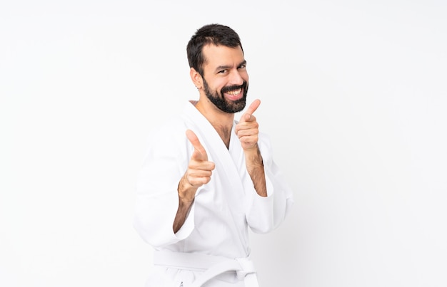Young man doing karate over isolated white pointing to the front and smiling