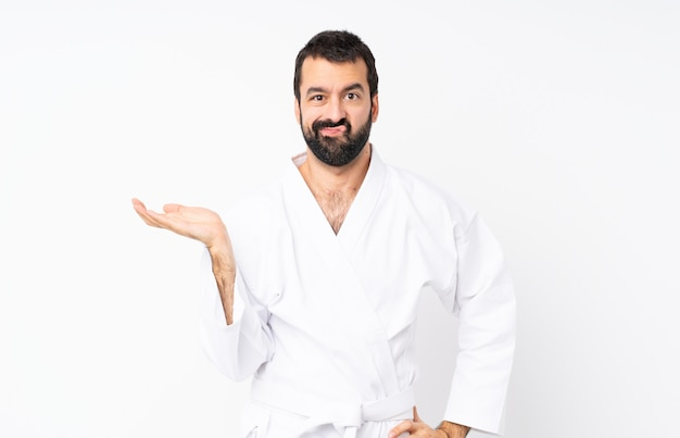 Young man doing karate over isolated white unhappy for not understand something