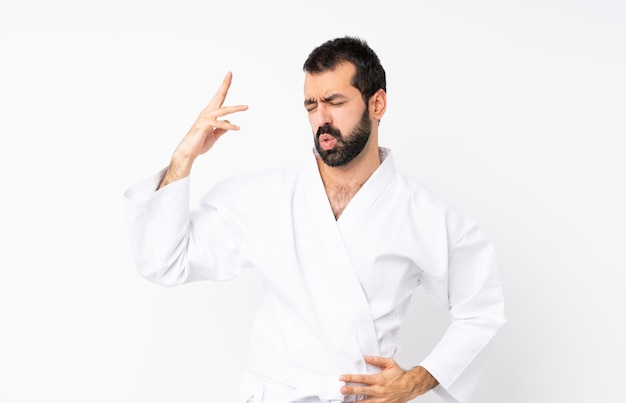 Young man doing karate over isolated  with tired and sick expression