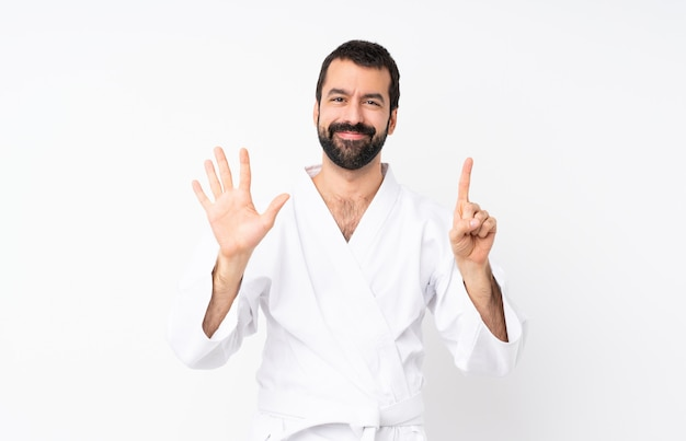 Young man doing karate over white counting six with fingers