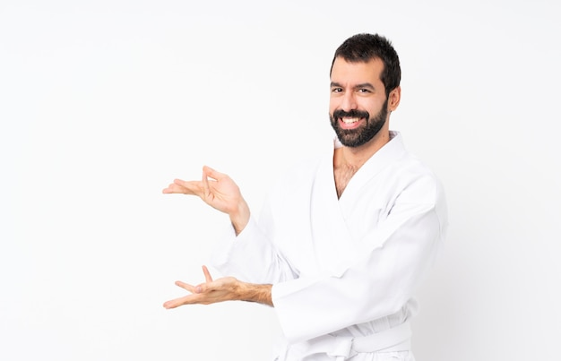 Young man doing karate over white extending hands to the side for inviting to come