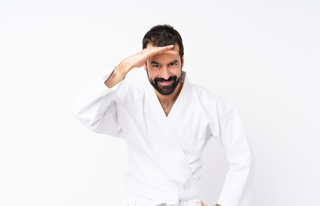 Young man doing karate over white looking far away with hand to look something
