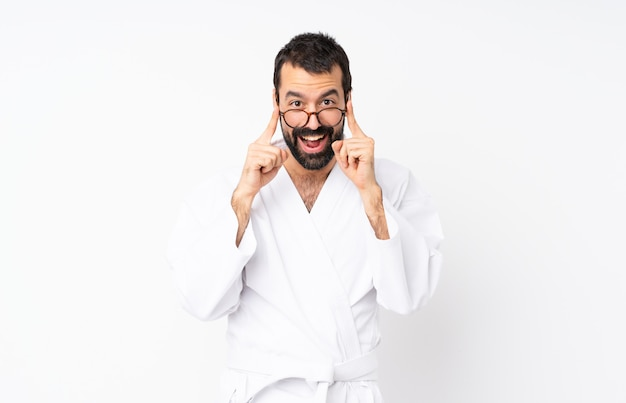 Young man doing karate over white with glasses and surprised