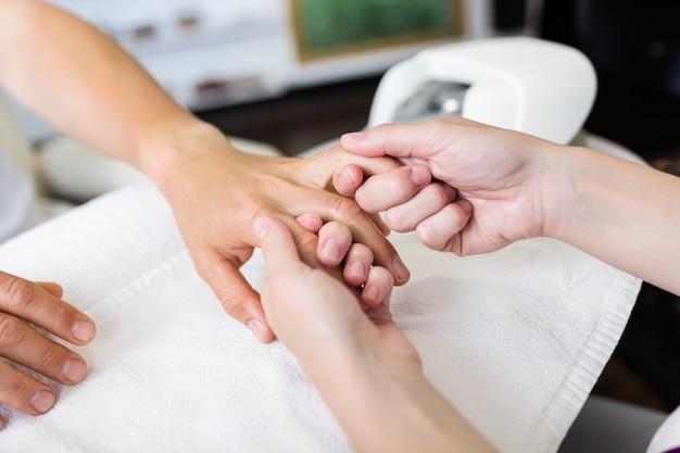Giovane uomo che fa manicure in salone. concetto di bellezza.