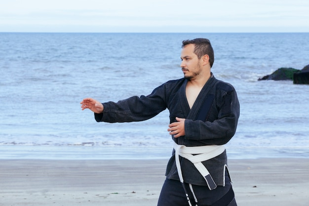 Young man doing martial arts isolated on the beach