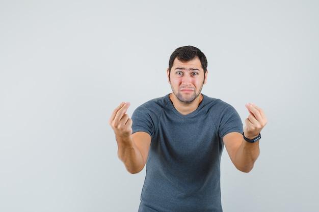 Молодой человек делает денежный жест в серой футболке и выглядит неимущим