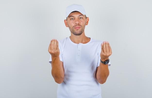 Молодой человек делает денежный жест руками в белой футболке, кепке, вид спереди.