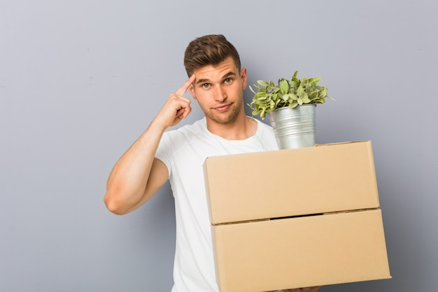 Young man doing a move holding boxes pointing his temple with finger, thinking, focused on a task.