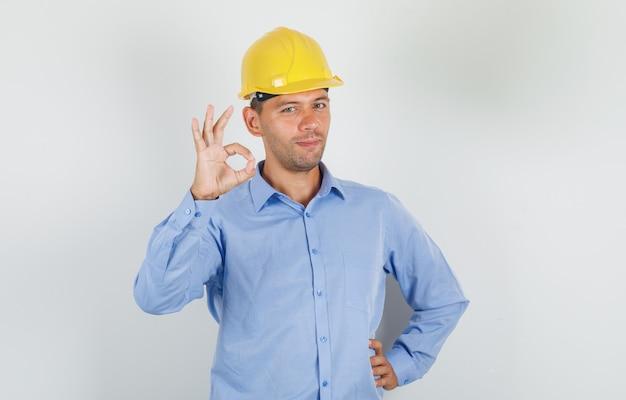 Молодой человек делает хорошо подписывается в рубашке, шлеме и выглядит счастливым