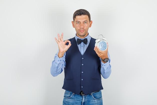 若い男がスーツ、ジーンズで目覚まし時計でokサインをして喜んで探しています。