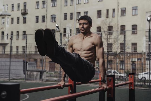 平行棒腹筋運動をしている若い男。