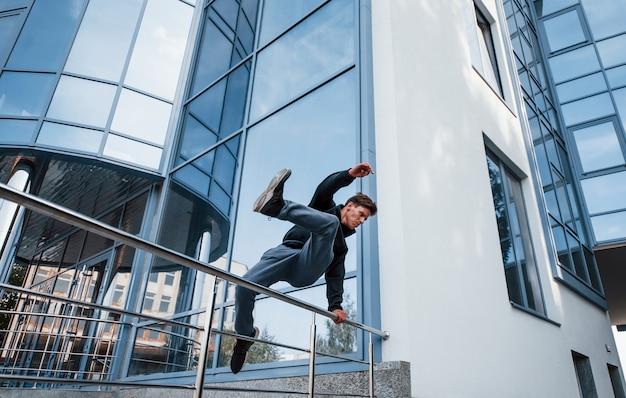 Молодой человек занимается паркуром в городе в дневное время. концепция экстремального спорта.