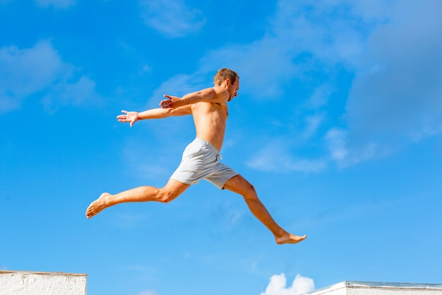 Young man doing parkour jump on the blue sky background on sunny summer day