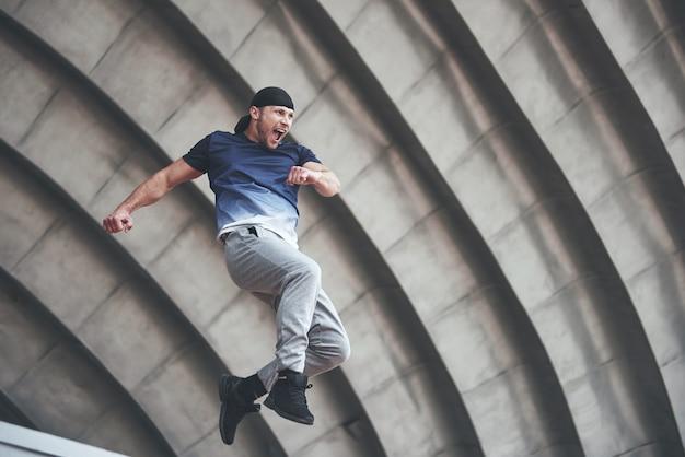 パルクールを行う若い男は都市の日当たりの良い春夏の日の都市空間でジャンプします。